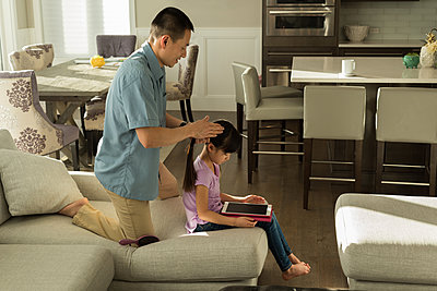 Girl using digital tablet while father combing her hair at home - p1315m1565966 by Wavebreak