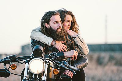 Portrait of couple on motorbike looking at distance - p300m2104273 von Oscar Carrascosa Martinez