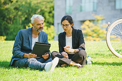 Serious business colleagues looking at mobile phone and discussing while sitting on grassy field - p301m1498731 by Halfdark