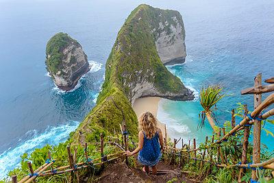 Blonde woman standing on cliffside steps admiring ocean coastline of Nusa Penida island, Bali, Indonesia - p343m1543761 by Konstantin Trubavin