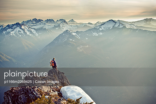 Hiker standing on the edge of a cliff looking out at scenic mountians - p1166m2269425 by Cavan Images