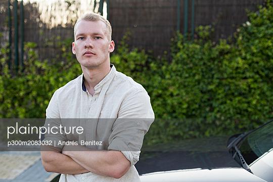 Portrait of young man standing beside car - p300m2083032 by Andrés Benitez