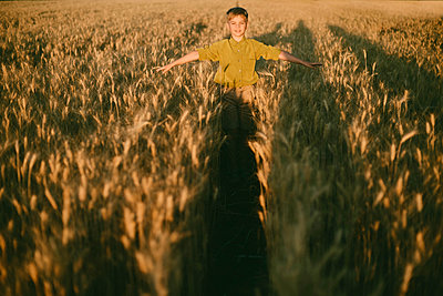 Carefree boy with arms outstretched standing amidst wheat field during sunset - p1166m1547016 by Cavan Images