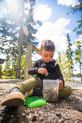 Young boy collects rocks in clear container outdoors. - p1166m2147331 by Cavan Images