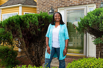 Smiling African-American woman standing in front of her house - p1166m2193838 by Cavan Images