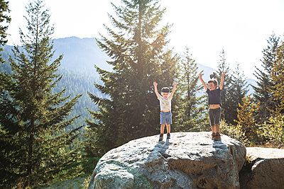 Two young hikers raise their hands in celebration, completing hike. - p1166m2212596 by Cavan Images