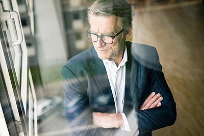 Serious mature businessman looking out of window - p300m2004099 von Joseffson