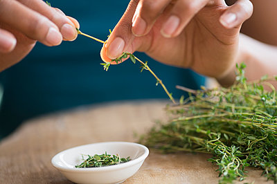 Mixed race woman trimming herbs - p555m1420242 by JGI/Jamie Grill