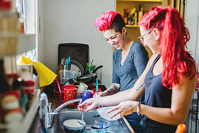 Two young women with pink hair laughing whilst washing dishes at kitchen sink - p924m1180185 by Lena Mirisola