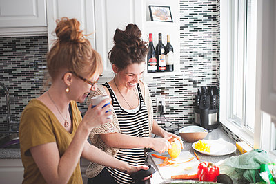 Two women preparing food in kitchen - p924m836533f by Hugh Whitaker