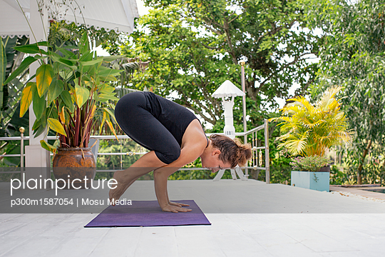 Woman practicing yoga on terrace - p300m1587054 von Mosu Media