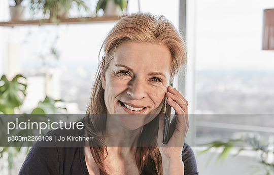 Beautiful smiling woman with brown hair talking on mobile phone in loft apartment at home - p300m2266109 by Jo Kirchherr