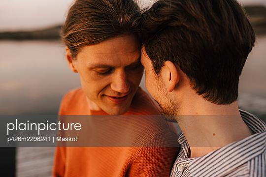 Gay couple doing romance at lakeshore - p426m2296241 by Maskot