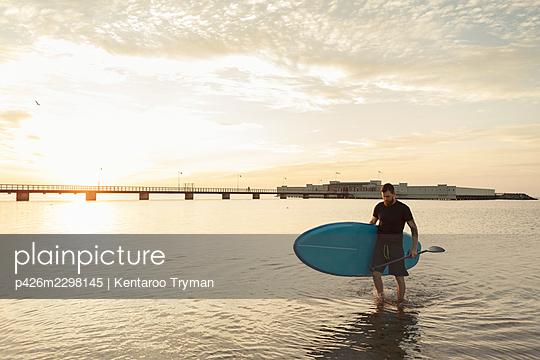 Mature man carrying paddleboard while walking in sea - p426m2298145 by Kentaroo Tryman