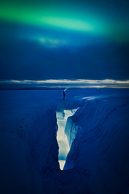 Person standing above an ice crevasse looking at the Aurora Borealis  - p1166m2130873 by Cavan Images