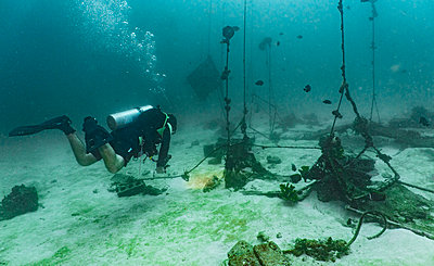 Diver checking out abounded lobster cages in Phuket - p1166m2136231 by Cavan Images