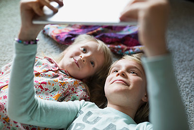 Smiling sisters taking selfie with digital tablet on floor - p1192m1145601 by Hero Images