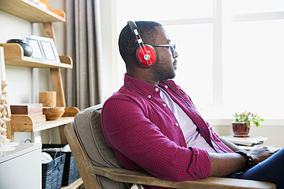 Man with headphones listening to music and looking away in living room - p1192m1201955 by Hero Images