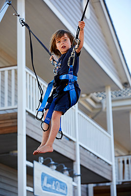 Boy on trampoline secured by bungee cord - p1511m2223077 by artwall