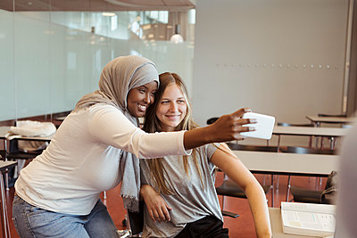 Smiling woman in hijab taking selfie with friend on smart phone at classroom - p426m2072289 by Kentaroo Tryman