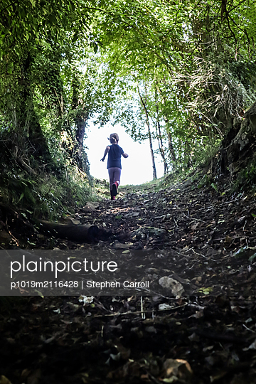 Girl running in  forest - p1019m2116428 by Stephen Carroll