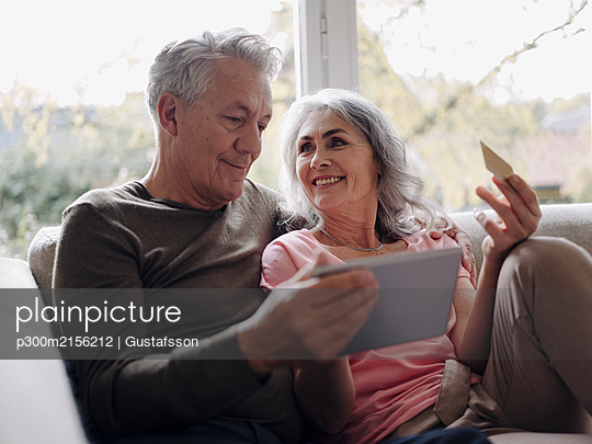 Happy senior couple relaxing on couch at home using tablet for online shopping - p300m2156212 by Gustafsson