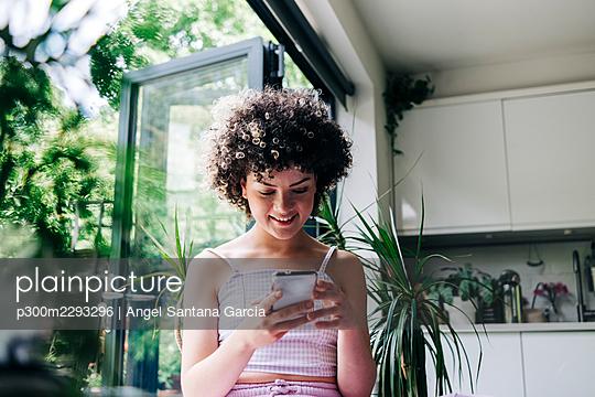 Smiling woman using smart phone at home - p300m2293296 by Angel Santana Garcia
