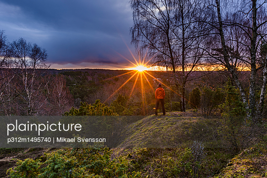 Hiker looking at sunset over forest - p312m1495740 by Mikael Svensson