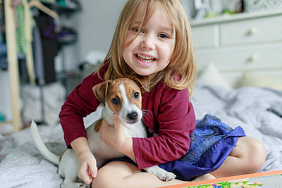 Portrait of happy little girl crouching on bed with Jack Russel Terrier puppy - p300m1563219 by Katharina Mikhrin