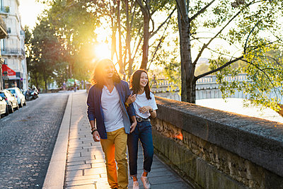France, Paris, happy young couple walking at river Seine at sunset - p300m2024126 von VITTA GALLERY