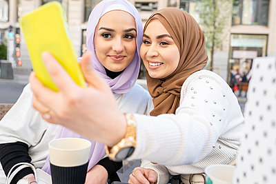 Young woman taking selfie through smart phone with female friend in city - p300m2275134 by Jose Carlos Ichiro