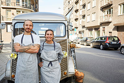 Portrait of confident male and female owners standing in front of food truck parked on city street - p426m1536961 by Maskot