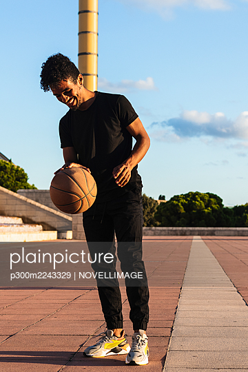 Smiling young man playing with basketball while standing on footpath during sunset - p300m2243329 by NOVELLIMAGE