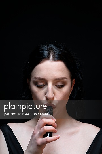 Young woman smoking electronic cigarette - p427m2181244 by Ralf Mohr