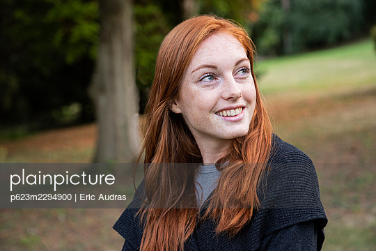 Smiling young woman sitting in public park - p623m2294900 by Eric Audras