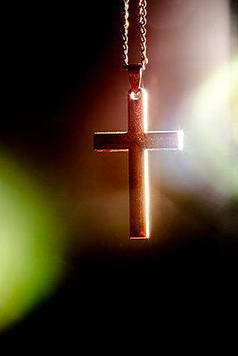 An old metal cross or crucifix hanging from a metal chain, a religious icon or symbol often used by the christian faith. - p1057m1572926 by Stephen Shepherd