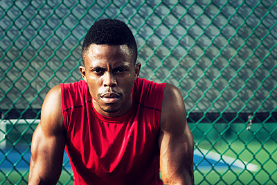 Portrait of confident male athlete against chain-link fence at field - p1166m1088133f by John Trice