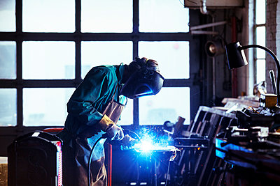 Worker welding in workshop - p1166m1209423 by Cavan Images
