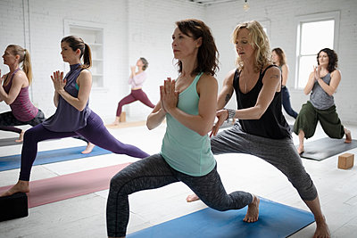 Yoga instructor guiding woman practicing warrior one pose - p1192m1583341 by Hero Images