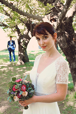 Bride with groom in background - p1521m2126364 by Charlotte Zobel