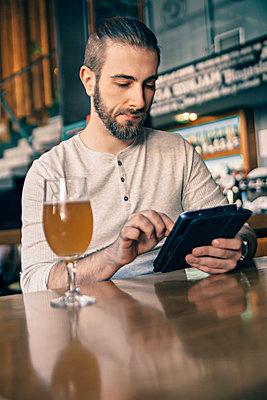 Man using digital tablet in a bar - p300m1101157f by Zeljko Dangubic