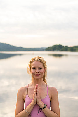 Portrait of smiling young woman at a lake - p300m2140556 by Joseffson