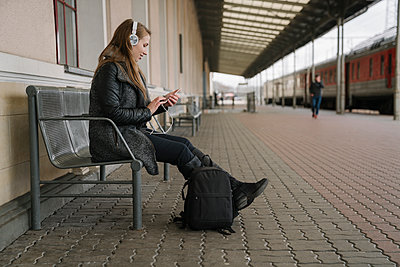 Smiling young woman with backpack sittting on platform using smartphone and headphones, Vilnius, Lithuania - p300m2155215 by Hernandez and Sorokina