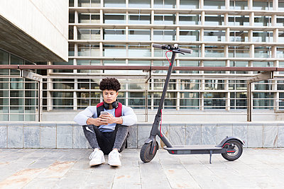 Young man with e-scooter relaxing and using smartphone - p300m2155372 by Sus Pons