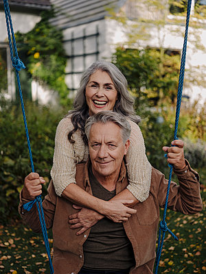 Happy woman embracing senior man on a swing in garden - p300m2156226 by Gustafsson