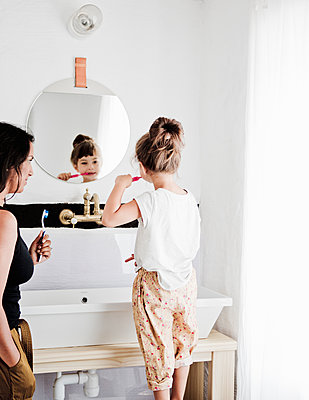 Sweden, Mother and daughter (4-5) brushing teeth in bathroom - p352m1349571 by Lina Roos