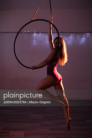 Female artist during a performance with hoop - p300m2023784 von Mauro Grigollo