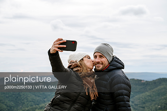 Woman kissing smiling boyfriend while taking selfie against sky during winter - p300m2250133 by VITTA GALLERY