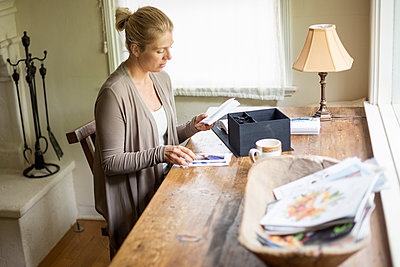 Blond woman sitting at a desk by a window, looking at  photographs. - p1100m1080235 by Mint Images