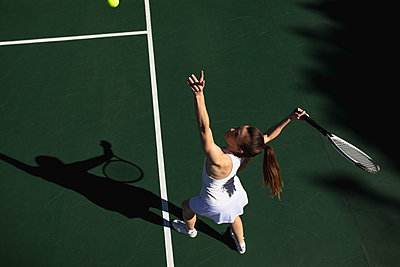 Woman playing tennis on a sunny day - p1315m2131513 by Wavebreak